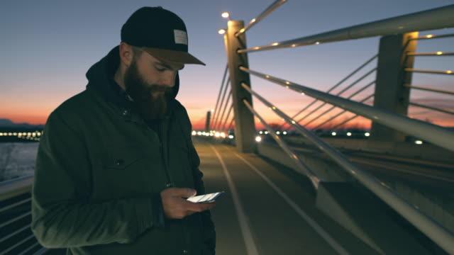 ms man using smart phone on bridge at dusk - convenience stock videos & royalty-free footage