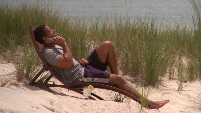 ms man using smart phone on lounge chair on beach, eastville, virginia, usa - ein mann allein stock-videos und b-roll-filmmaterial