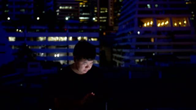 mann mit smartphone auf dach in der nacht - blick nach unten stock-videos und b-roll-filmmaterial