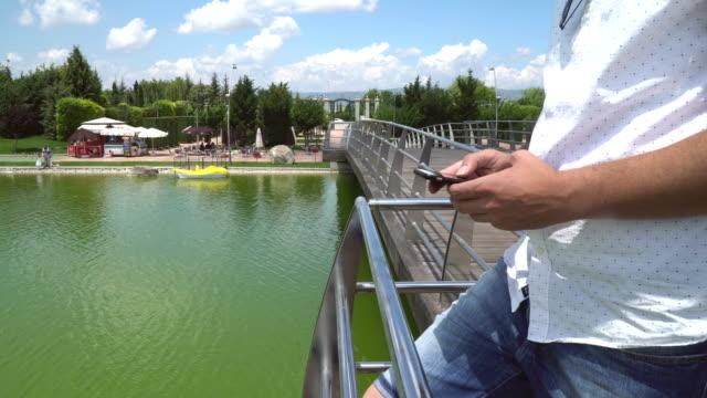 橋の上のスマート フォンを使用している人