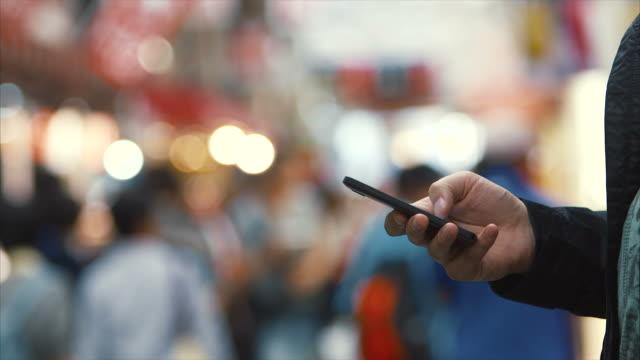 vídeos de stock, filmes e b-roll de homem usando telefone inteligente na rua (câmera lenta) - extremo oriente