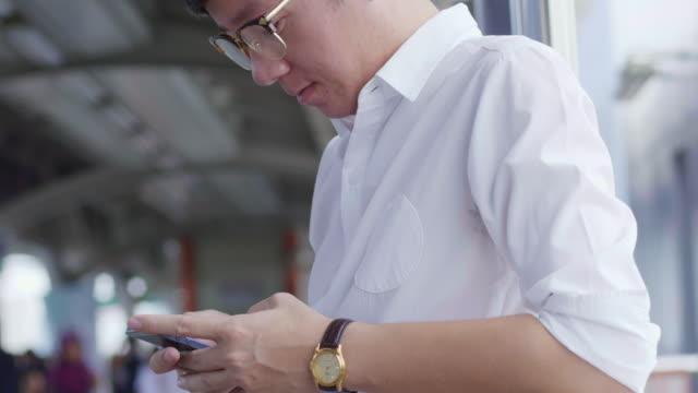 vídeos y material grabado en eventos de stock de hombre usando teléfono inteligente en la estación de metro - desplazamiento
