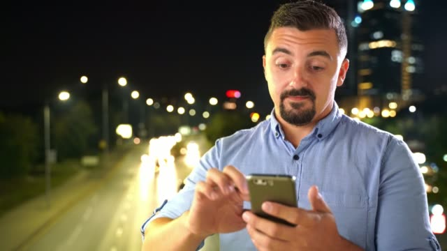 Man using smart phone outdoors at night in front of city traffic lights