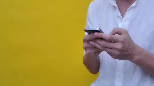 vídeos y material grabado en eventos de stock de hombre usando el estudio de teléfono inteligente filmado en el fondo amarillo - camisa blanca