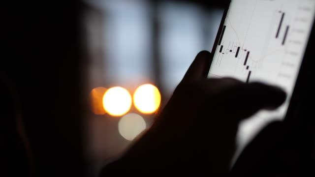 vídeos de stock, filmes e b-roll de homem usando telefone inteligente para analisar o gráfico de ações - comercializar