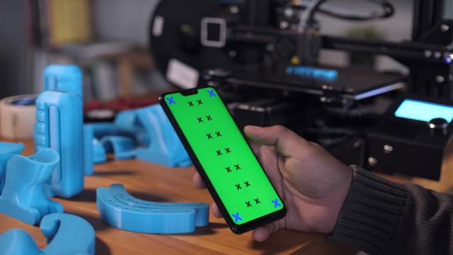 stockvideo's en b-roll-footage met mens die slimme telefoon met groen scherm op bureau in 3d printer labroratory gebruikt - ingesproken bericht