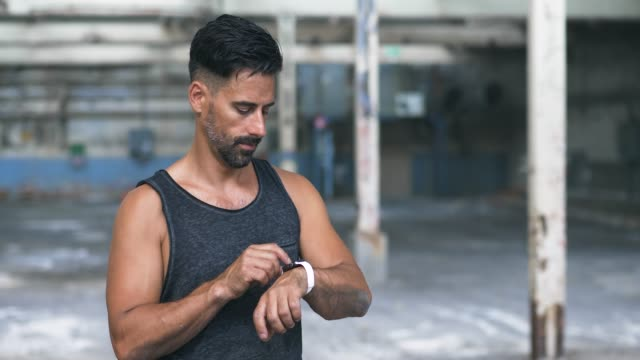 Man using Smart Watch during Exercise in Abandoned Warehouse