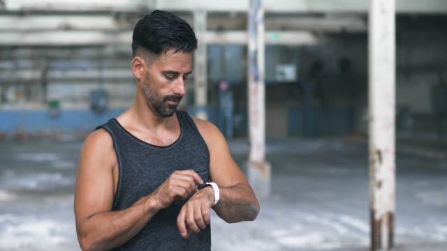 vídeos y material grabado en eventos de stock de hombre usando smart watch durante el ejercicio en el almacén abandonado - parte del cuerpo humano