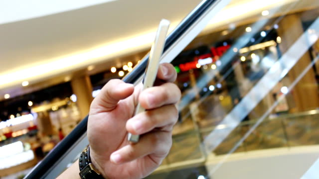 man using smartphone and touch screen in shopping mall