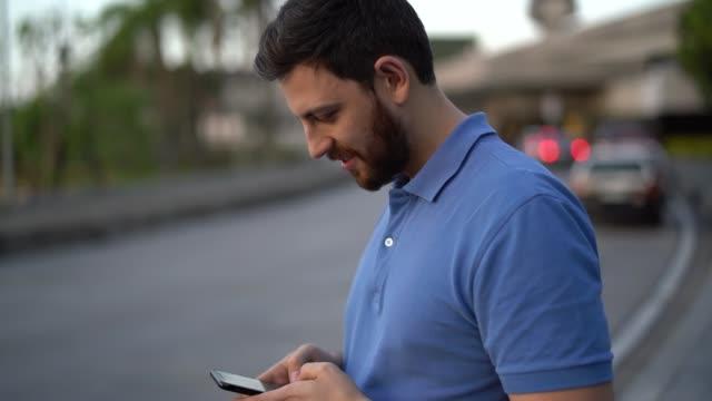 vídeos de stock, filmes e b-roll de homem que usa o smartphone e que espera o carro - text