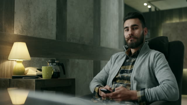 Man using smartphone at home