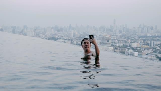 man använda smartphone vid poolen - utebassäng bildbanksvideor och videomaterial från bakom kulisserna