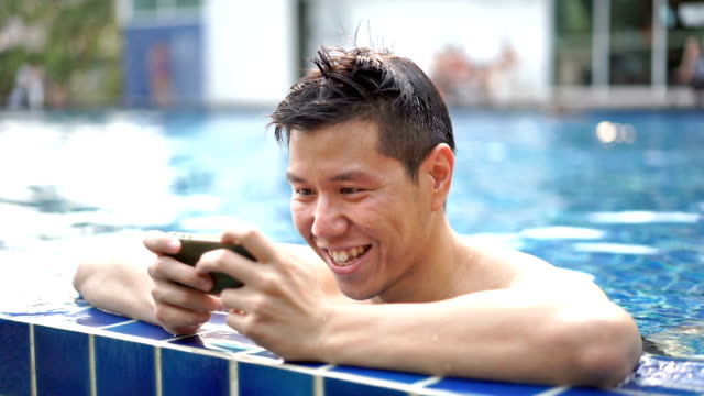 Man using smartphone by the swimming pool