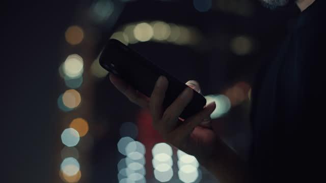 vídeos y material grabado en eventos de stock de hombre usando teléfono inteligente en la ciudad por la noche - un solo hombre