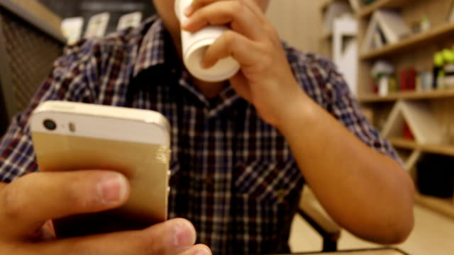 man using smartphone in coffee shop (cafe)
