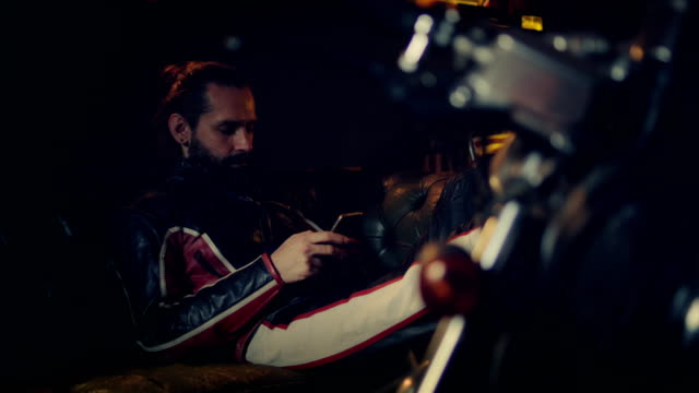 man using smartphone in motorcycle workshop - motocross stock videos & royalty-free footage