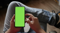 Man Using Smartphone in Vertical Mode with Green Mock-up Screen, Doing Swiping, Scrolling Gestures. Guy Mobile Phone, Internet Social Networks Browsing News, Financial Reports. Point of View Camera.
