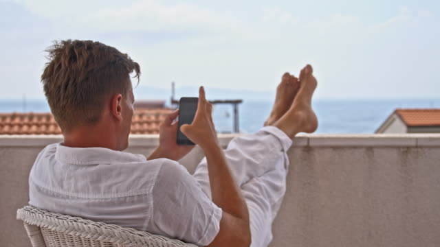 DS Man using smartphone on the balcony