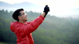 Man using smartphone to take a photo and video at the top of mountain with river view