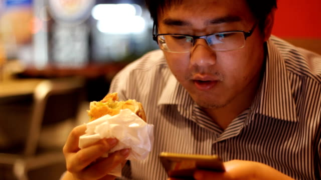 man using smartphone while eating hamburger - decapitated stock videos & royalty-free footage