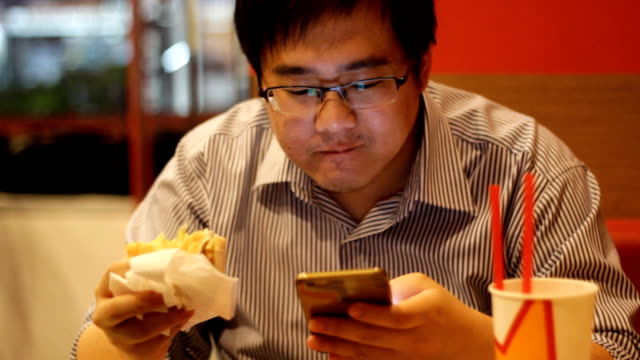 man using smartphone while eating hamburger