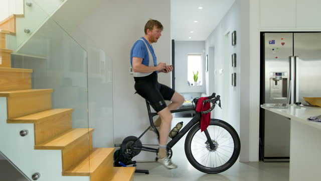 man using smartphone whilst on indoor bike turbo trainer - domestic kitchen stock videos & royalty-free footage