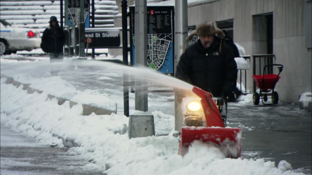 MS ZO PAN Man using snow blower to clear sidewalk in front of business / New York, New York, United States