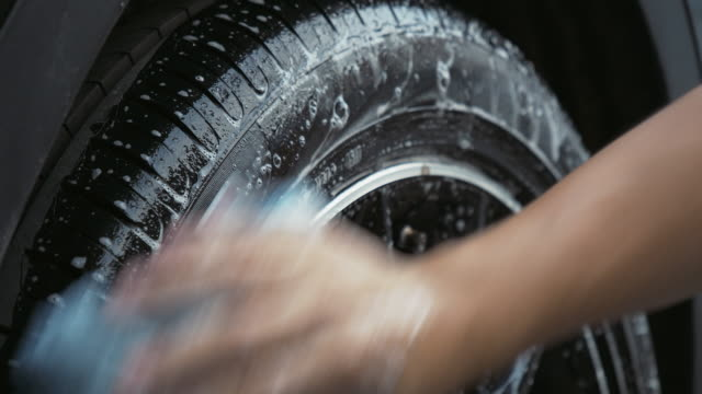 man using sponge washing car tire. - dirty stock videos & royalty-free footage
