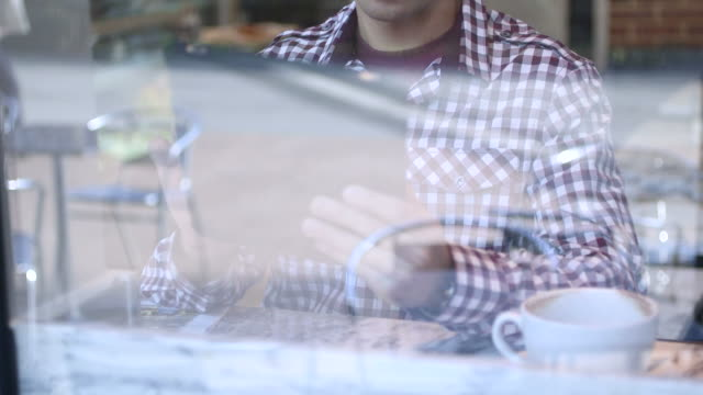 Man using tablet and drinking coffee