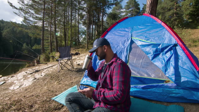 vídeos de stock e filmes b-roll de man using tablet at campground - cama de campanha
