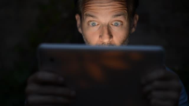 Man Using Tablet at Night