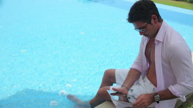 MS Man using tablet computer at poolside,Mallorca