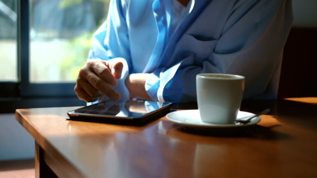 man using tablet for social media on table and drinking coffee in cafe - kindle stock videos & royalty-free footage