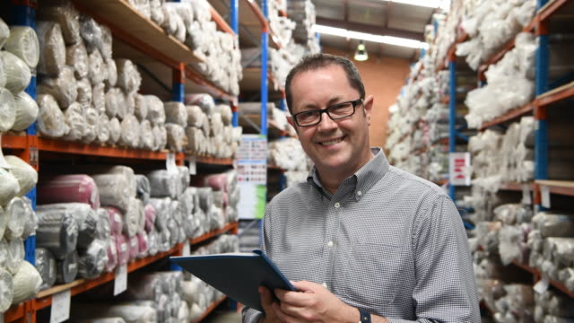 Man using tablet in carpet warehouse and turning towards camera