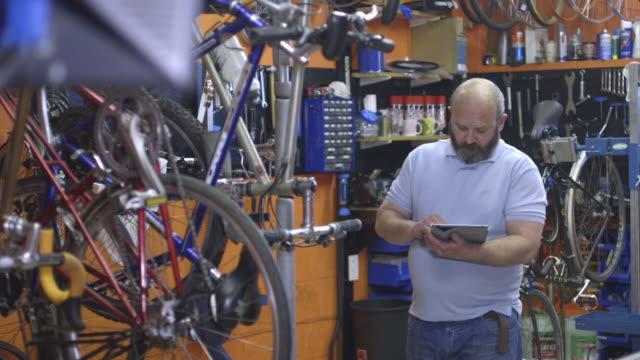 stockvideo's en b-roll-footage met man using tablet in workshop - greater london