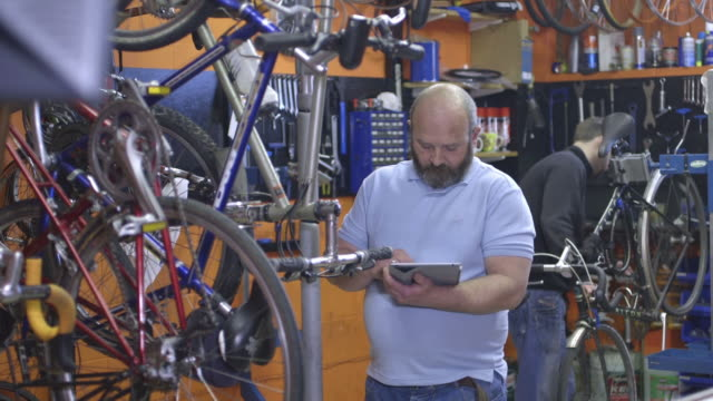 man using tablet in workshop - 40 seconds or greater stock-videos und b-roll-filmmaterial