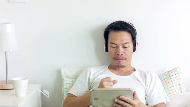 男性のタブレットを使用してベッド - 30代点の映像素材/bロール