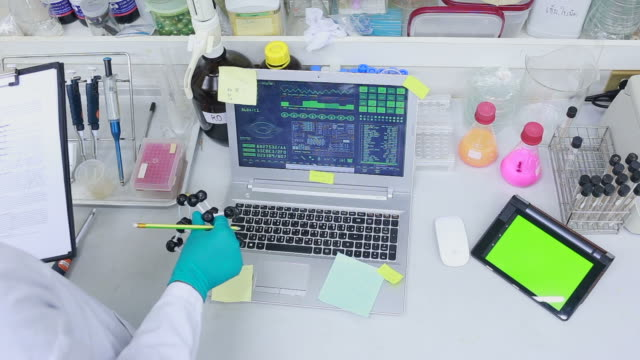 Man using tablet pc against medical lab. Top view