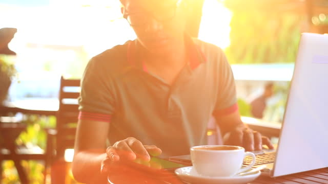 Man Using Tablet PC and Drinking Coffee in Cafe