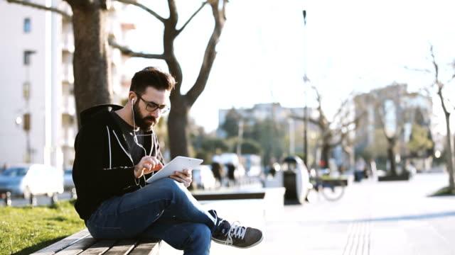 Man using tablet pc on public park
