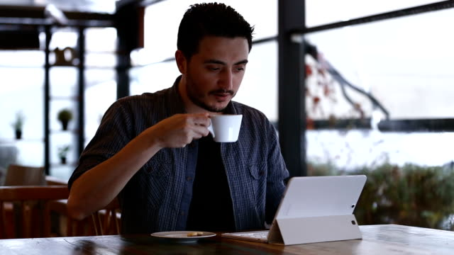 Man using tablet Pc with coffie