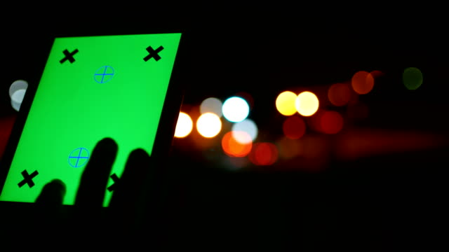 man använder tablet pc med grön skärm med oskärpa trafik ljus bakgrund - injicera bildbanksvideor och videomaterial från bakom kulisserna