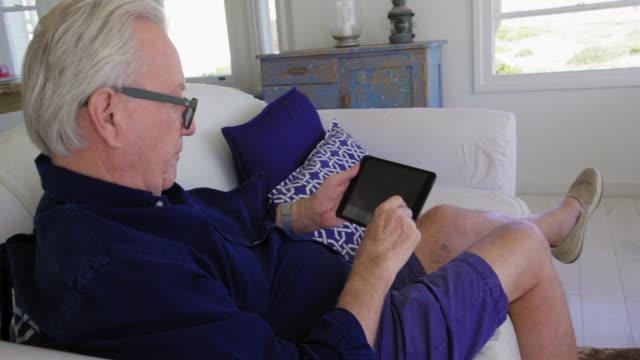 vídeos de stock e filmes b-roll de man using tablet - idoso na internet