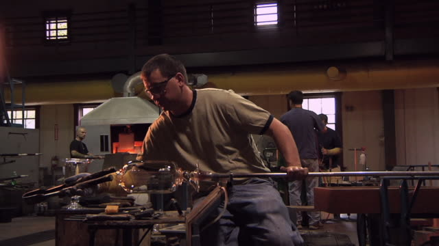 MS Man using tongs to shape reheated glass into vase at glass blowing factory / Windsor, Vermont, USA