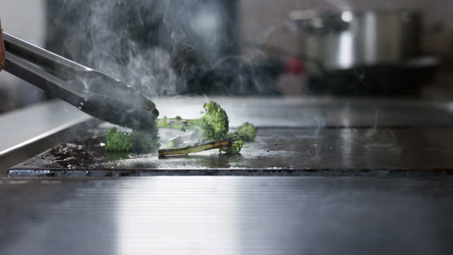 man using tongues on hot plate cooking brocolli - unrecognisable person stock videos & royalty-free footage
