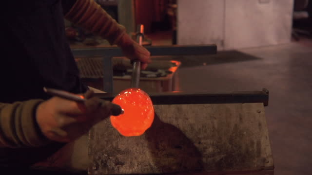 cu tu td man using tool to create texture in glass bowl at glass blowing factory / windsor, vermont, usa - glasbläser stock-videos und b-roll-filmmaterial