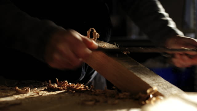 CU man using traditional tools to hand craft wood in his workshop