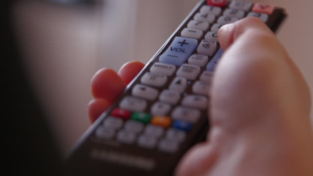 vidéos et rushes de man using tv remote control - critique