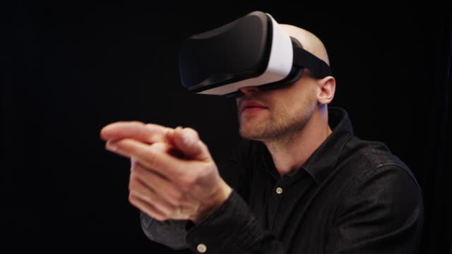 vídeos de stock e filmes b-roll de man using virtual reality glasses. aiming with imaginary weapon - arma de fogo