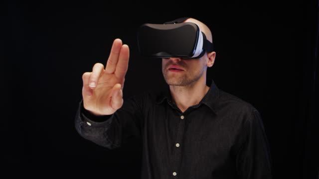 vidéos et rushes de homme à l'aide de lunettes de réalité virtuelle. découverte et cueillette des éléments - touche de couleur